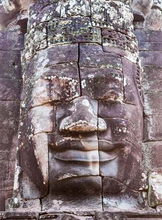 prasat bayon: Stone smiling face in Prasat Bayon, part of Angkor Khmer temple complex, among tourists ancient landmark and place of worship in Southeast Asia Siem Reap, Cambodia Stock Photo