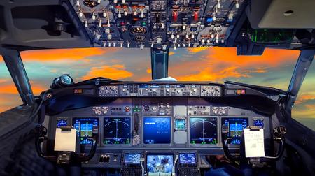 piloto de avion: cabina de avión cubierta de vuelo en la puesta del sol
