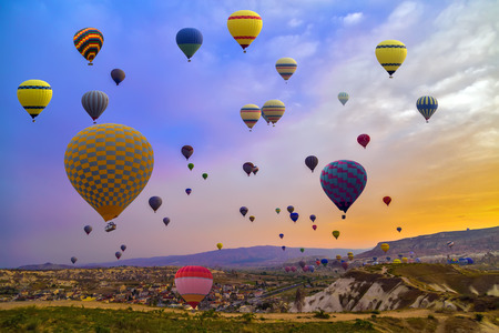 Hot Air balloons flying over Mountains landscape sunset Cappadocia, Turkey 스톡 콘텐츠