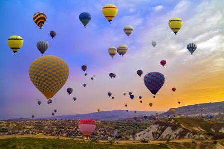 Heteluchtballonnen vliegen over Bergen landschap zonsondergang Cappadocië, Turkije Stockfoto