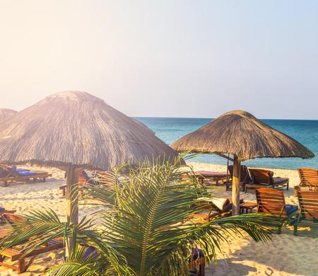 beachfront: beach lounge chairs under tent on beach, vintage nature background