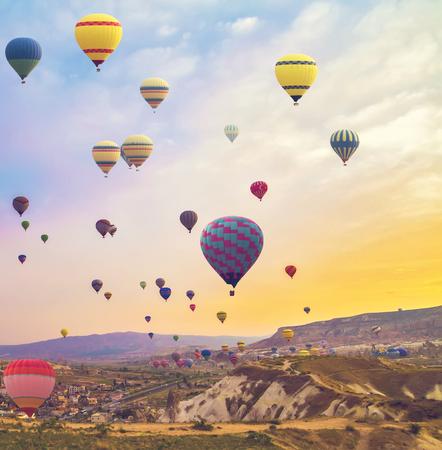 Hete lucht ballonnen vliegen over bergen landschap zonsondergang Cappadocië, Turkije, vintage aard achtergrond