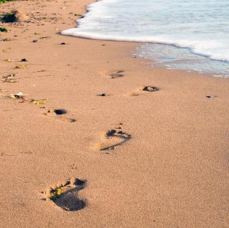 Foot prints on a gold sandy beach