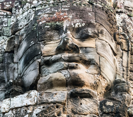 Stone smiling face in Prasat Bayon, part of Angkor Khmer temple complex, among tourists ancient landmark and place of worship in Southeast Asia Siem Reap, Cambodia Stock Photo
