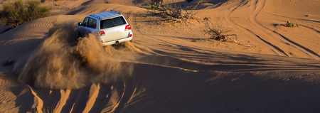 Safari rally off-road car 4x4 adventure driving in the desert sand dune is a popular activity among tourists in Dubai.