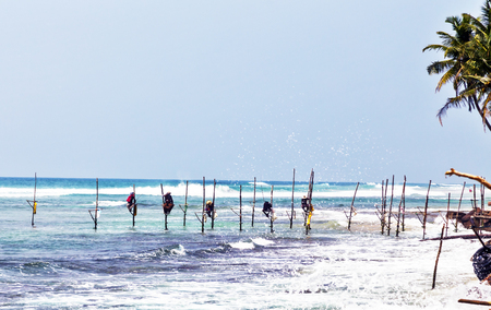 Silhouettes of the traditional fishermen, Local traditional stilt fishermen fishing rod in Indian ocean, Sri Lanka. Stock Photo