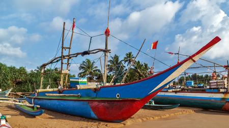 Sri Lankan traditional fishing catamarans, Colorful fishing boats on a long sandy beach on the ocean coast of Sri Lanka. Stock Photo