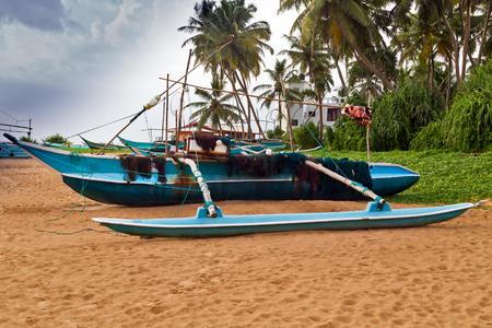 Sri Lankan traditional fishing catamarans, Colorful fishing boats on a long sandy beach on the ocean coast of Sri Lanka. Popular landmark fishing Ceylon village.