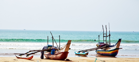 OLD traditional fishing catamarans, Colorful fishing boats on a long sandy beach on the ocean coast of Sri Lanka. Popular landmark fishing Ceylon village.