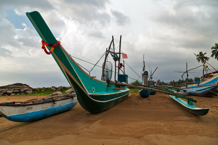Sri Lankan traditional old fishing catamarans, Colorful fishing boats on a long sandy beach on the ocean coast of Sri Lanka. Popular landmark fishing Ceylon village. Stock Photo