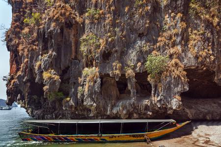 Traditional old thai long-tail boat on beach island in andaman sea, cave limestone rock, Phuket, Krabi, Khao Phing Kan Pang Nga bay, South of Thailand. Stock Photo