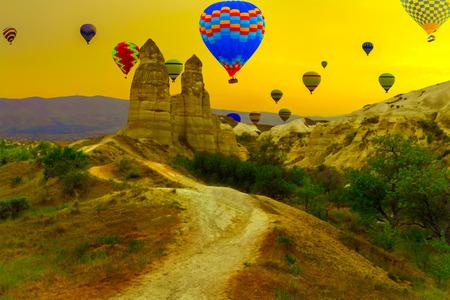 Love valley Hot air balloons landing in a mountain, landscape at Cappadocia Turkey