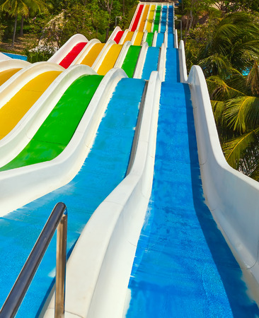 The Multi colorful plastic water-slide in swimming pool Water Park Stock Photo - 91090170