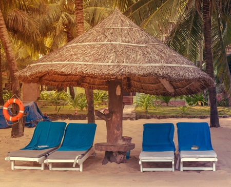 Blue sunbeds Deckchairs, umbrella and chair, parasol on the tropical sand beach
