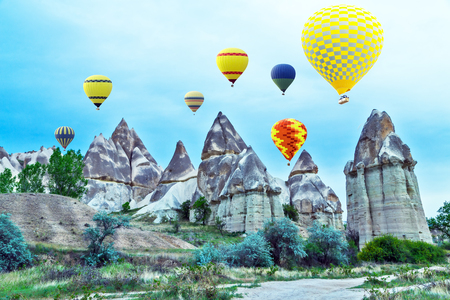 Hot air balloons flying in sunset mountain landscape in Cappadocia, Goreme National Park, Turkey. Travel background Stock Photo