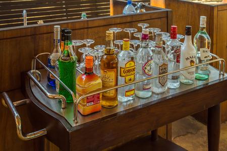 SRI LANKA, UNAVATUNA - 21 FEBR 2016: Bottles of assorted selection at a restaurant bar, ready to make mixed cocktails brands Martini, Johnnie Walker, Captain Morgan, Beefeater, Smirnoff vodka, Bacardi, Original Gordons London Dry Gin on wooden table.