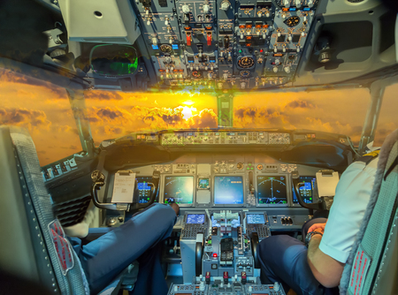 airplane Instrument panels cockpit Flight Deck in Amazing sunset incredible foamy waves. Фото со стока