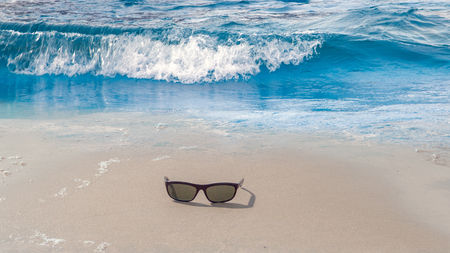 sunglass spectacles, eyeglass glass silhouette over white sand beach Caribbean sea wave Tropical landscape, Summertime seascape