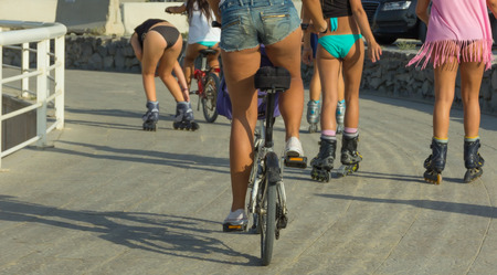 Pretty Young sexy woman roller skates, girls riding a bicycle Active outdoors people. Healthy spring living Sports concept