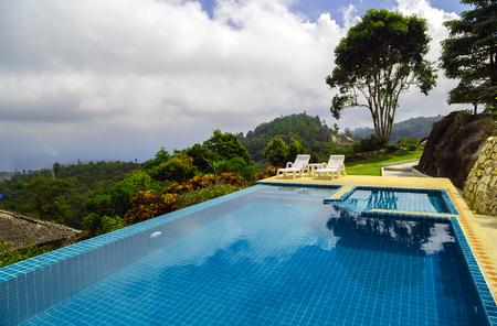 Hotel beach chair swimming pool blue water at spa resort Reklamní fotografie - 121047001