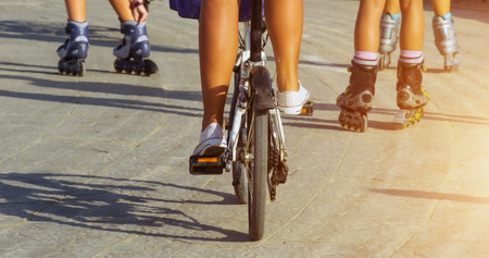 Pretty girl riding on roller skates bicycle posing on the road, Active outdoors people street during sunset. Healthy spring living Sports concept Imagens
