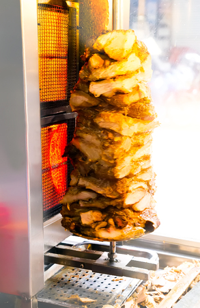 Istanbul street food Doner Kebab made of meat cooked on a vertical hot rotisserie. traditional Turkish dish - Shawarma meat grilled. Traditional fast food. (soft focus)