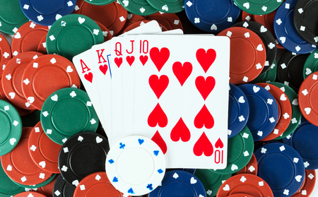 Casino gambling chips playing cards royal flush in hearts background