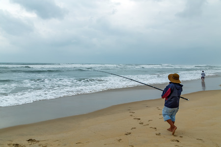 Fisherman with hat on the beach with fish rod, fishing in ocean from beach on sunset. big game fishing trip 写真素材