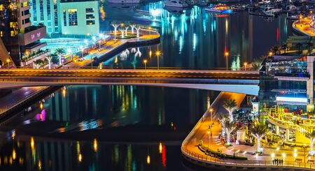 Dubai, UAE - January 24, 2016: Dubai Marina aerial panoramic view cityscape by night, illuminated skyscrapers bridge and the persian gulf.