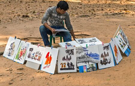 SIEM REAP, CAMBODIA - March 01, 2015: Street artist sell paintings drawings of the picture Angkor Wat is a popular tourist attraction