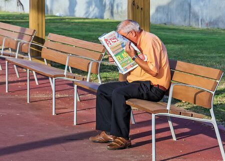 BARCELONA, SPAIN - August 22, 2012: Grandfather pensioner sit outdoors in park, senior man reading the latest news Newspaper.