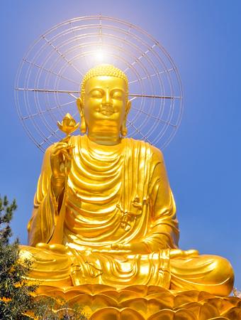 Statue stone Buddha sitting on blue sky Thien vien Van Hanh in Dalat city in Vietnam. Buddhist holiday - Happy Bodhi day achieved enlightenment. Stock Photo