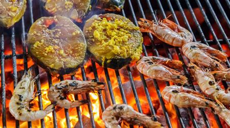 Cerrado de camarones asados, langostinos a la barbacoa de comida callejera y rodajas de salmón. Foto de archivo