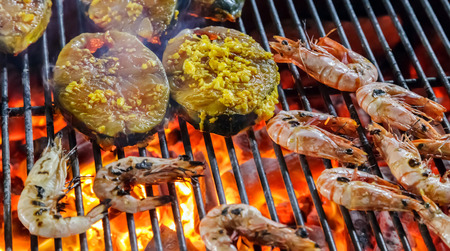 Closed up of shrimp roast, street food BBQ prawn and salmon slices. Фото со стока