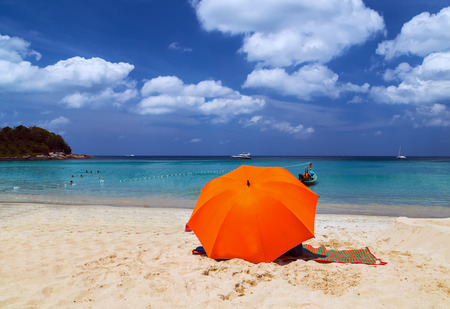 Beach Umbrella. Red sun parasol on the tropical sand beach exotic vacation seascape. concept of leisure. Stock Photo