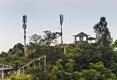 Radio broadcast tower communication antenna. in jungle mountains, Catba national park attractions. Cat ba island in Halong bay, Vietnam Stock Photo