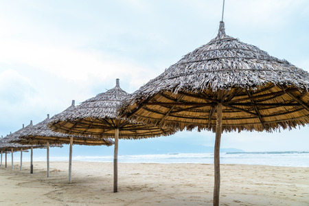 umbrella made of palm leafs parasol on the tropical sand beach exotic vacation seascape concept of leisure.