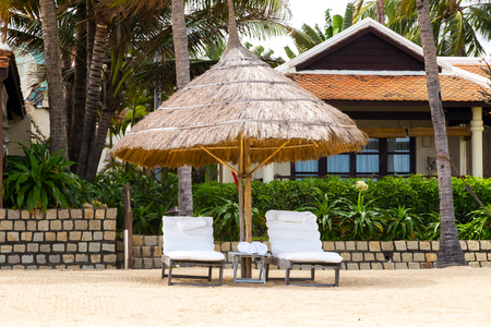 Deckchairs Beach Umbrella made of palm leafs chair parasol on the tropical place for relax and vacations.