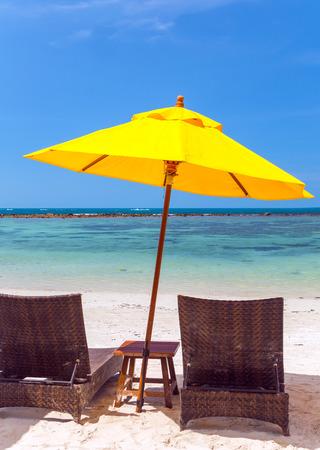 Deckchairs Beach Umbrella. chair parasol on the tropical sand beach exotic vacation seascape concept of leisure. Фото со стока