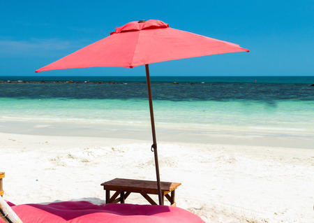 Deckchairs umbrella and chair parasol on the tropical sand beach exotic vacation seascape. concept of leisure. Stock Photo