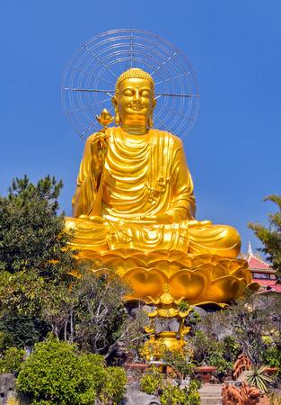 Statue gold Buddha sitting on blue sky Thien vien Van Hanh in Dalat city in Vietnam. Buddhist holiday - Happy Bodhi day achieved enlightenment.