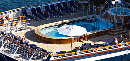 Sunbathers relaxing on the open deck cruise ship in the sea. Summer vacation Cruise travel tourism concept. Ship cruise liner deck blue waves sea view romantic landscape.