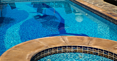 Swimming pool water blue glass mosaic with staircase at hotel