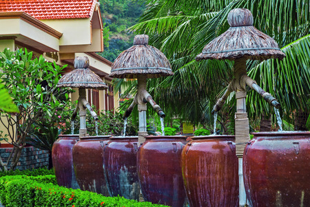 Cafe restaurant resort terrace with palms on the source of spring mineral water jug. Drinking water falls source. Paradise fountain pouring water weaving wooden in clay pitcher, terracotta pots. Reklamní fotografie