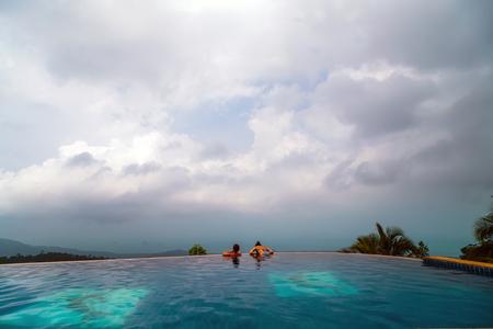 Blue glass mosaic swimming pool. relaxing in infinity swimming pool looking 版權商用圖片