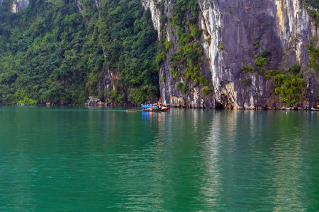 Tourist boat panorama high cliff most popular landscape for travel Vietnam. Halong Bay Tour Cruise Discover Rock islands spectacular limestone.