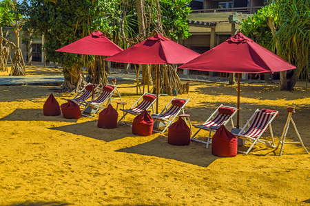 Deckchairs umbrella and chair parasol on the tropical sand beach exotic vacation seascape concept of leisure.