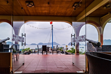 Restaurant sea terrace panoramic view seascape. interior terrace summer cafe. terrace by the seaside. canon on a gun carriage, wooden chairs and table. Cat Ba , Halong Bay, Vietnam Foto de archivo
