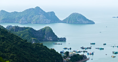 Fishing boat Halong bay islands mountains in South China Sea, Vietnam. Tourist attraction of Halong bay islands, spectacular limestone karsts, grottos natural cave formations. 写真素材