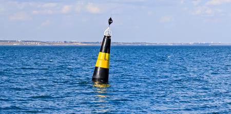 Schwimmende Navigationsboje. Marineboje im blauen Meerwasser, um die Schiffe zu warnen Standard-Bild